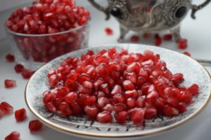 Pomegranates arils on a ceramic plate surrounded by loose arils and a glass bowl full of arils in the background