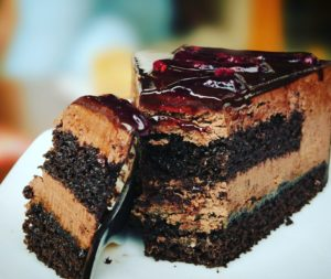 A slice of chocolate cake with chocolate ganache and icing