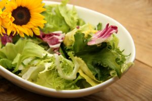 Salad mix with iceberg lettuce and flower garnish in white ceramic bowl