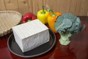 A whole block of tofu on a round wooden plate surrounded by a stalk of broccoli and three bell peppers